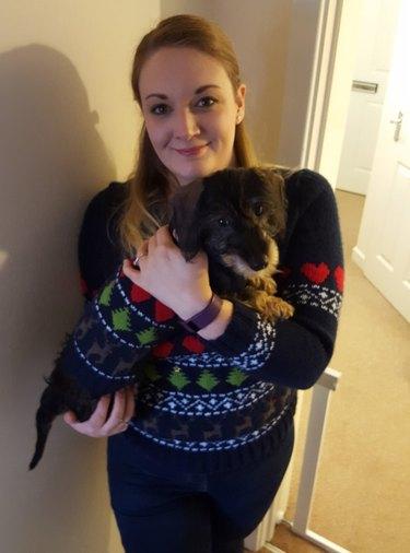 Woman holding dog wearing matching winter sweaters.