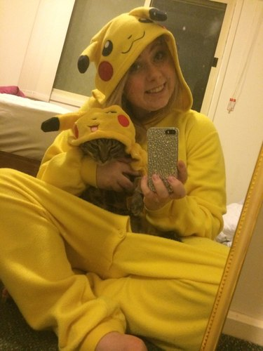 Woman in a Pikachu onesie takes selfie in mirror with cat in matching onesie