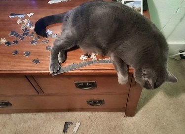 Cat lying on partially completed puzzle.