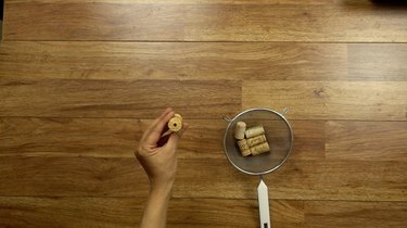 Boring holes into corks for DIY cat toys out of wine corks.