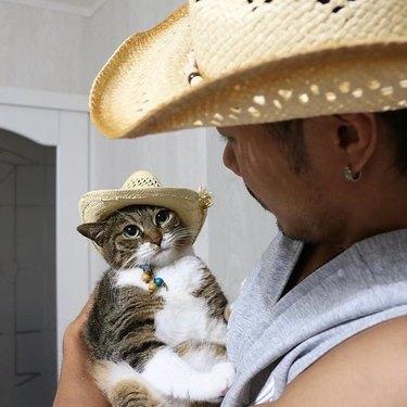 Man holding cat wearing matching straw hat