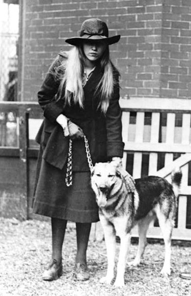Anna Roosevelt Halstead poses with her German Shepherd next to a fence