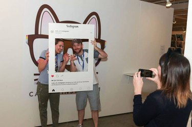 Couple poses for picture in Cats Of Instagram Lounge at CatCon
