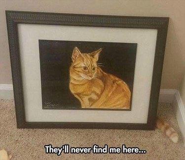 Cat hides behind portrait of cat