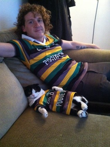Man and cat wearing matching rugby shirts