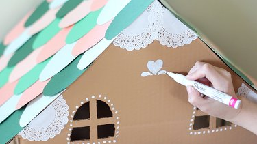 Drawing designs on house with paint pen