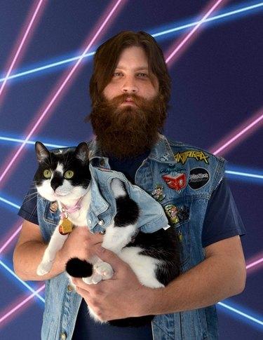 Man holding cat wearing denim vests in front of a laser background