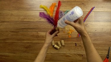 Gluing feathers to cork for DIY cat toys out of wine corks..
