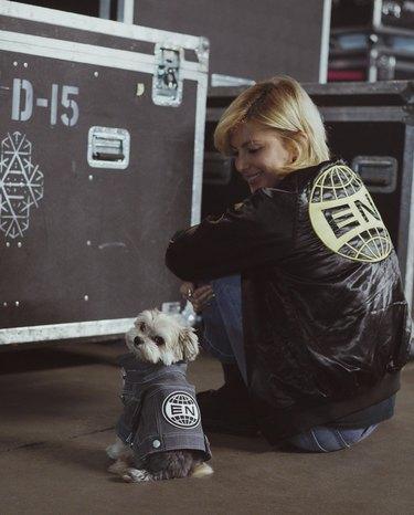 Women and small dog wearing matching jackets.