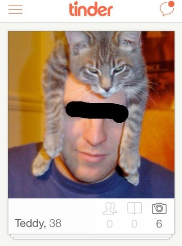 Man wears cat on head like hat