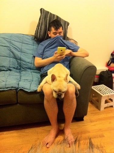 Man with dog in his lap covers his nose with a t-shirt.