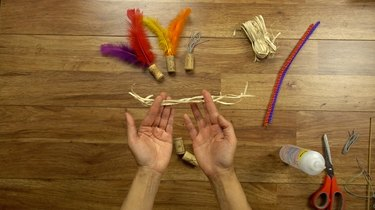 Cutting raffia for DIY cat toys out of wine corks.