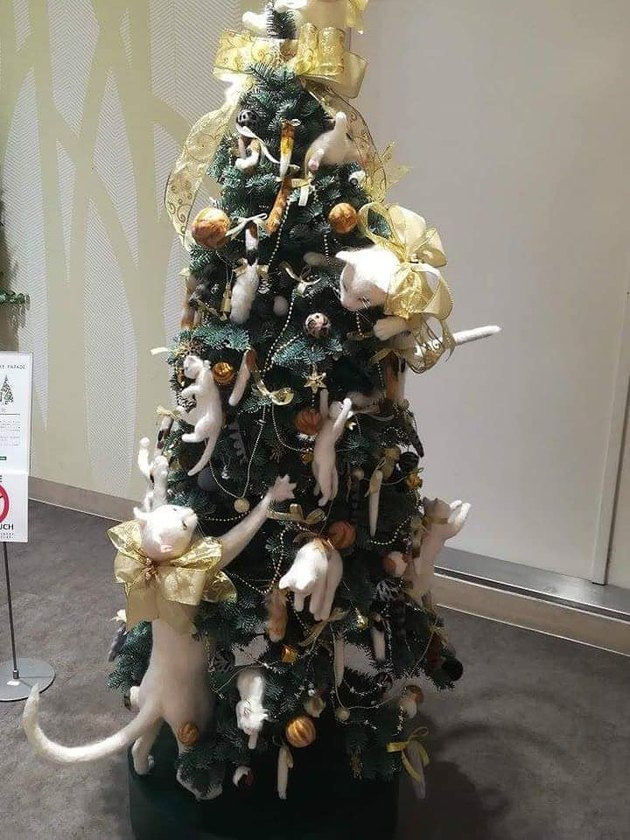 Christmas tree decorated with felts cats climbing all around it