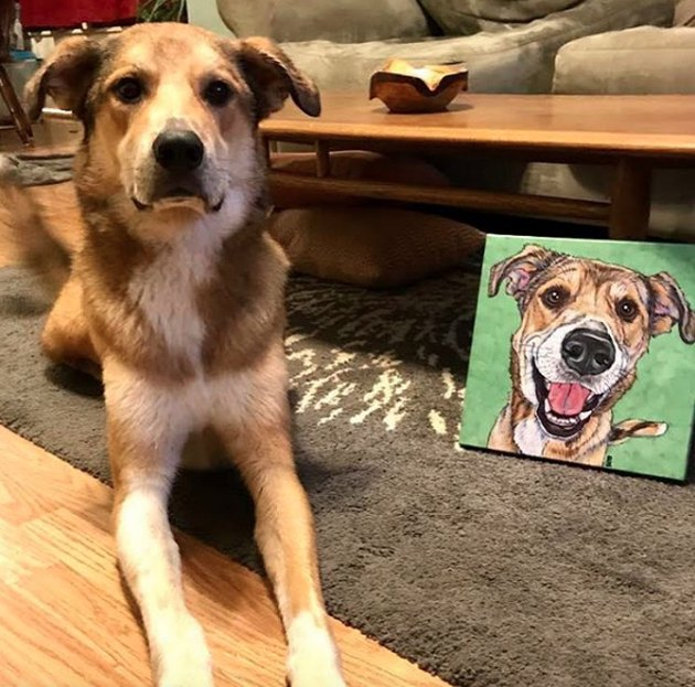 dog lying next to his custom portrait