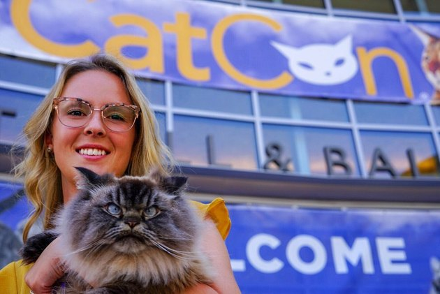 woman and cat pose in front of CatCon entrance