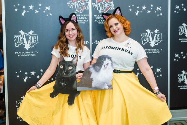 two women in yellow skirts, white shirts and cat ears posing with cat cutouts