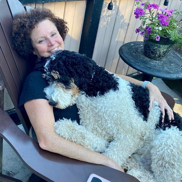 woman cuddles with big dog