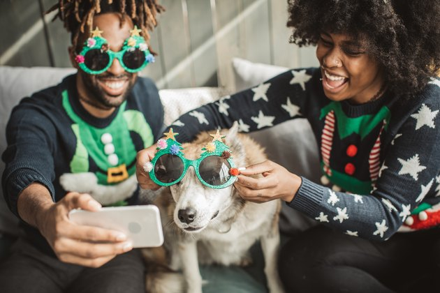 two people celebrating Christmas with their dog