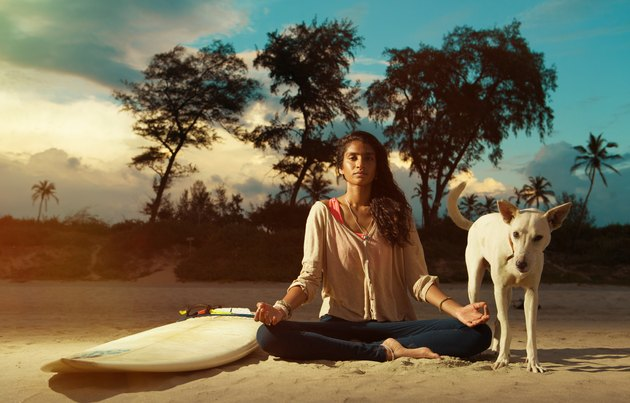 Indian surfer girl meditating in lotus pose