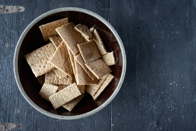 graham crackers in mixing bowl on dark wood table