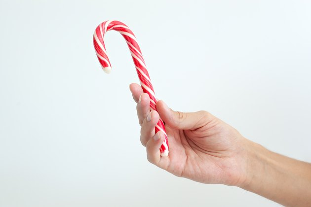 Male hand holding christmas candy cane