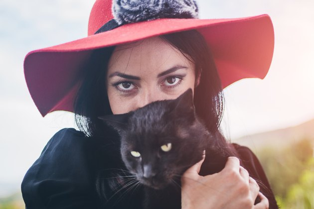 Young beautiful glamorous black-haired woman holding black cat