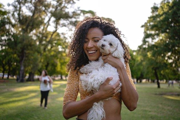 Joyful Latin American woman hugging her dog
