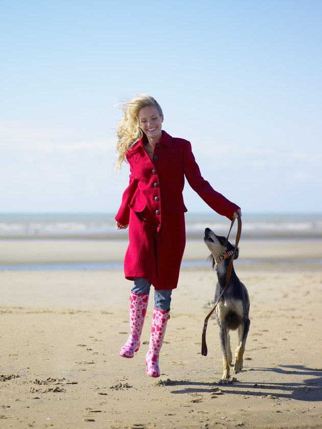 Woman skipping with dog on beach