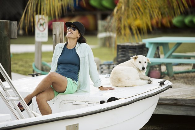 Woman sitting with dog on motorboat