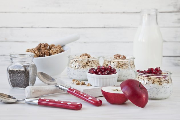 Ready-made healthy breakfast - muesli or granola with pomegranate, chia seeds and fresh natural yoghurt on white rustic wooden background, close-up, selective focus, shallow depth of field