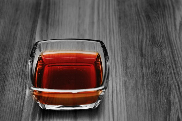 Soy sauce in a glass bowl on a wooden surface