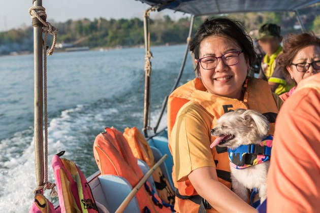 Portrait Of Smiling Woman Sitting With Dog On Boat In Sea
