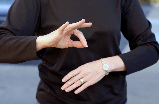 A woman using sign language wearing a black shirt