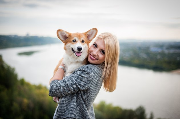 young woman smiling at camera holding corgi dog