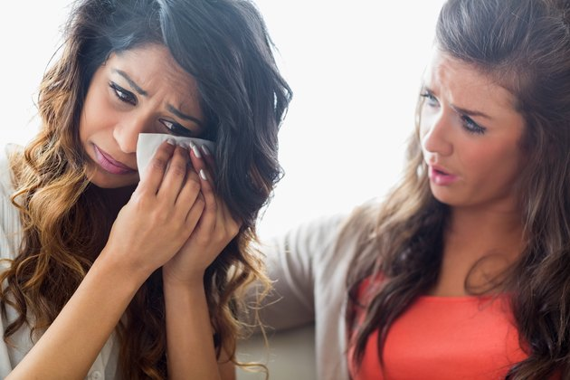 Girl crying and being consoled