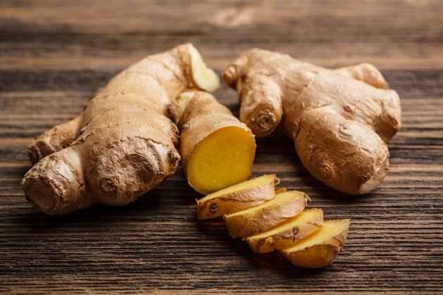 Fresh ginger whole and chopped on rustic wood surface