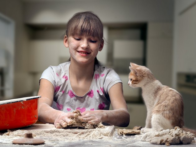 Funny girl kneads dough. kitten sitting next to.