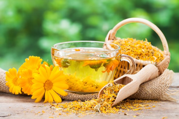 Cup of  marigold tea and calendula flowers.