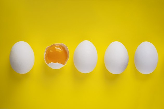 Four whole eggs and one broken egg on yellow background