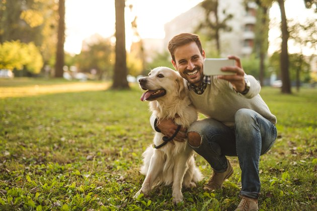 man taking selfie with dog outdoors