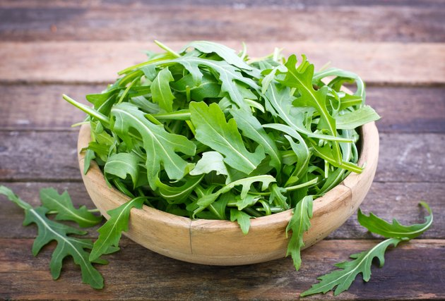 Fresh arugula salad in wooden bowl