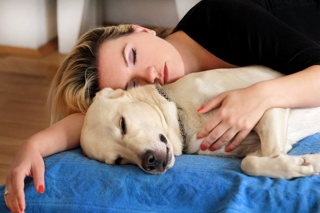 Woman sleeping next to cute dog on bed