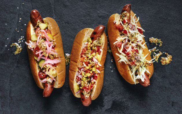 Three gourmet hot dogs on black background