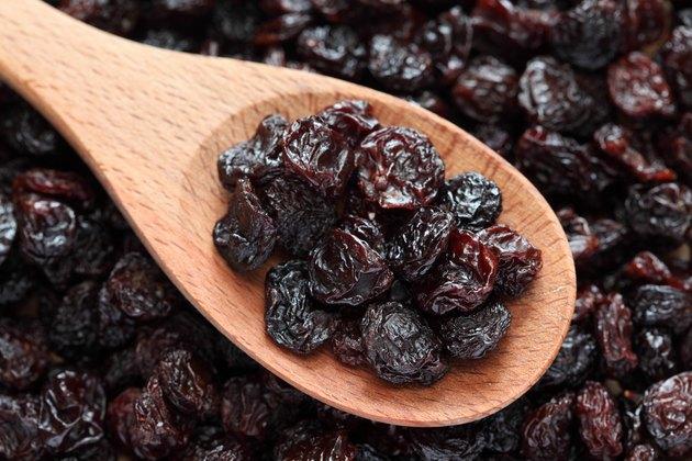 Purple raisins on a wooden spoon