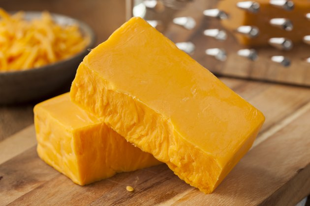 Organic Sharp Cheddar Cheese block with grater in background
