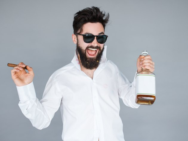man holding a bottle of whiskey and cigar