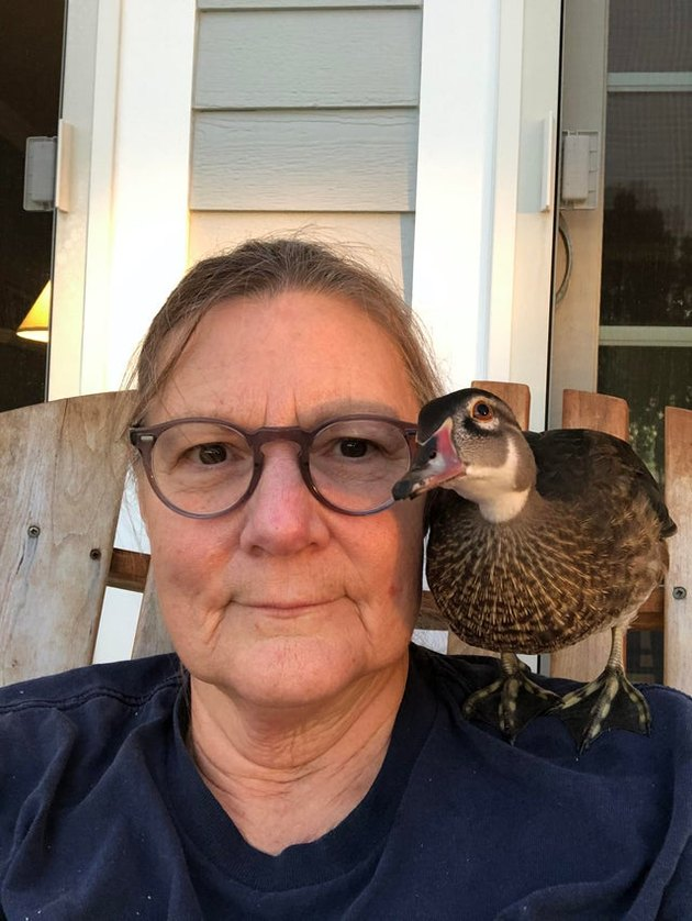 Woman with duck sitting on her shoulder
