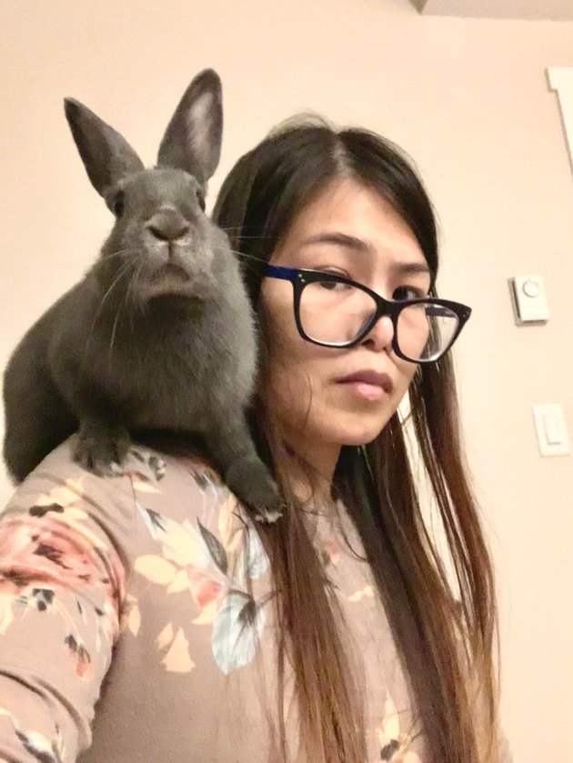 Woman with rabbit sitting on shoulder