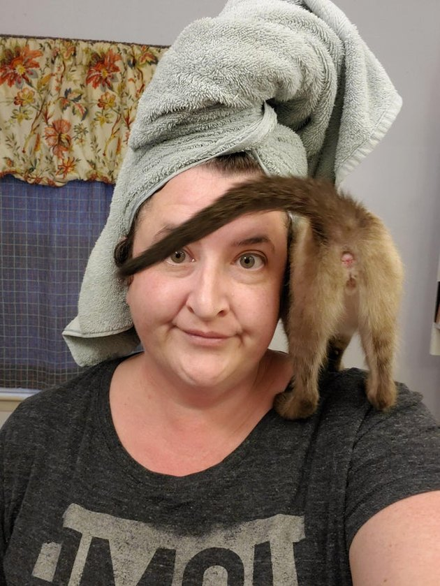Woman with kitten standing on shoulder with its butt facing forward
