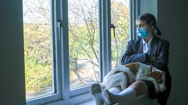 Schoolgirl with face mask looking out the window